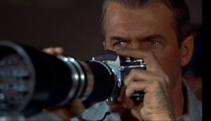 James Stewart using his camera to spy on his neighbors.